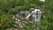 Wide view of luxuriant vegetation surrounding waterfall cascading on rocks