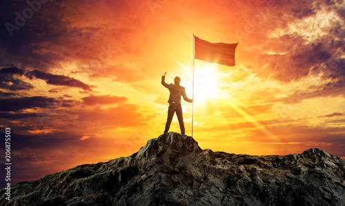 Businessman with flag on mountain top. Concept for success. Wallpaper Mural