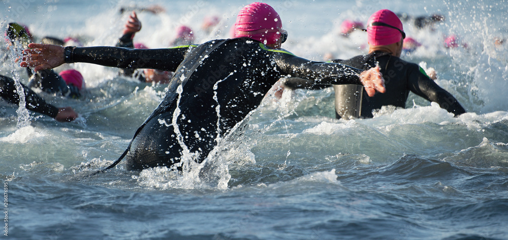 Fototapety, obrazy: Group triathlon participants running into the water for swim portion of race,splash of water and athletes running