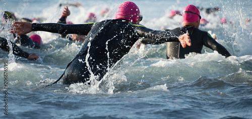 Fotografía  Group triathlon participants running into the water for swim portion of race,spl