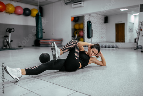 Fotografie, Obraz  Young woman doing bicycle crunches at the gym.