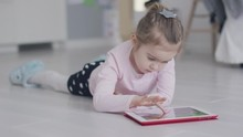 Little Casual Girl Lying On Floor At Home And Tapping On Tablet While Playing Interesting Game Looking Totally Absorbed.