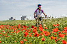 Nice Senior Woman Riding A E-Mountainbike In The Suburb Of A Big City, Surrounded By Green Fields And Red Poppies