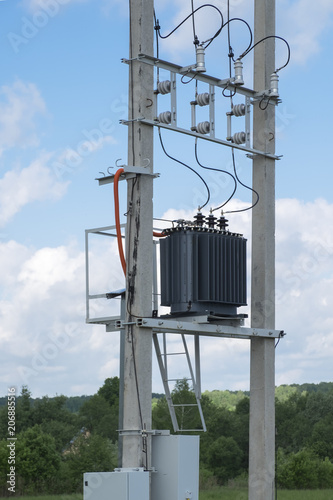 Photo Electric transformer stands on concrete supports.