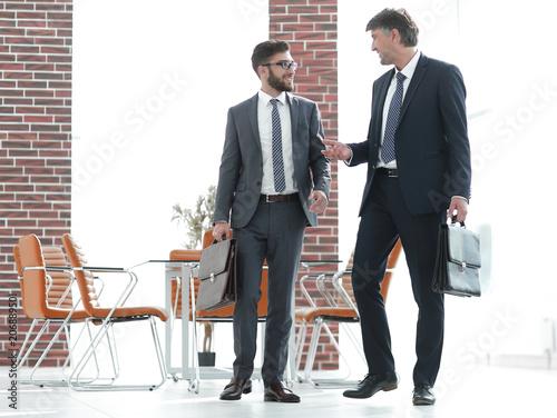 Fotografie, Obraz  Two businessmen walking along in modern office building