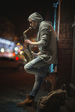 A Street Musician Plays The Saxophone In The Evening City
