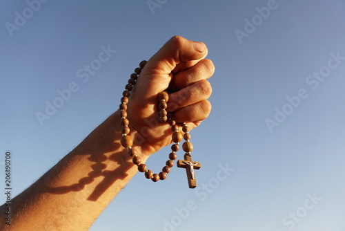 Valokuva rosary in the hand of a man on the background of the sky