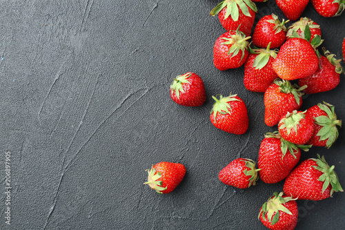 Ripe red strawberries on black background, top view