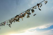 A Lot Of Pairs Of Shoes Hung On A Rope For Tied Shoelaces, Against A Cloudy Sky