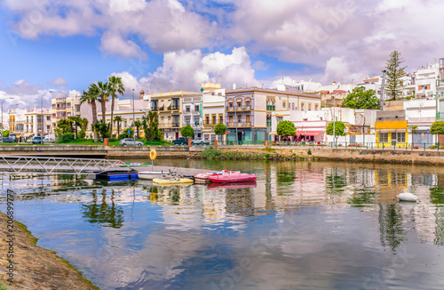 Traditional white architecture of the region along the riverbank in Ayamonte, Huelva province, Andalucia, Spain. There are pleasure paddle boats on river that runs into the Guadiana River. Ayamonte