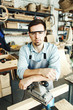 Portrait of confident young woodworker in protective eyeglasses looking at camera while leaning on sanding machine in his workshop