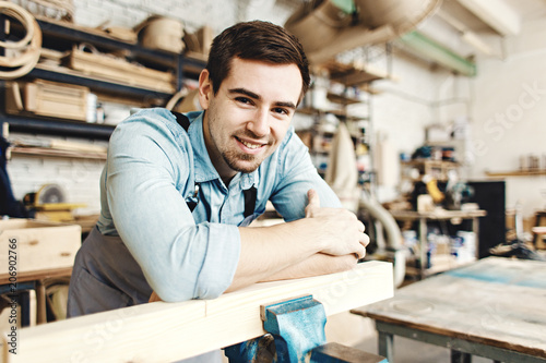 Fototapety, obrazy: Portrait of cheerful handsome furniture maker leaning on wood plank in his workshop and smiling at camera