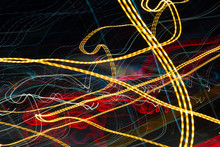 On A Dark Background Of Multicolored Lines, A Yellow Broken Ribbon Intersects The Center.