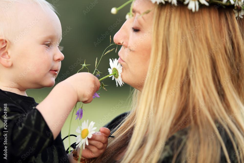 Fototapeta Mała dziewczynka bawi się białymi kwiatkami dotykając twarzy matki.