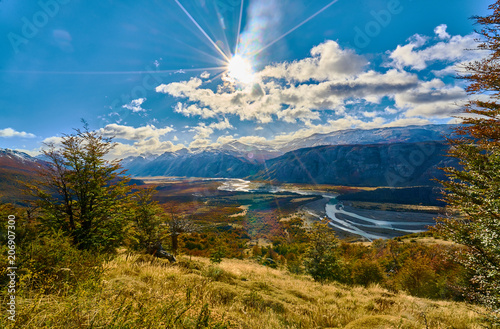 Foto op Aluminium Bergen A view of the mountains and the valley, which illuminates the autumn sun making its way through the clouds. Argentine Patagonia in Autumn
