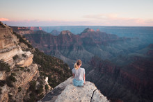 Grand Canyon, USA: Young Attractive Girl Sits On The Edge Of The Cliff, Enjoys Sunset