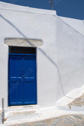 Photo Traditional wooden blue door and a white stone wall in Amorgos