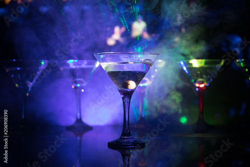 Fotobehang Bar Several glasses of famous cocktail Martini, shot at a bar with dark toned foggy background and disco lights. Club drink concept