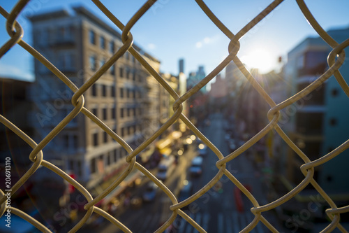 Fototapeta Downtown Manhattan and Chinatown viewed through a chainlink fence at sunset on the Manhattan Bridge. obraz