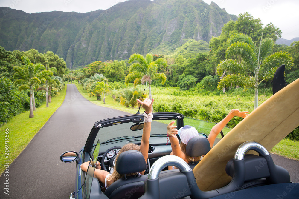 Fototapeta Road trip travel - girls driving car in freedom. Happy young girls cheering in convertible car on summer Hawaii vacations.