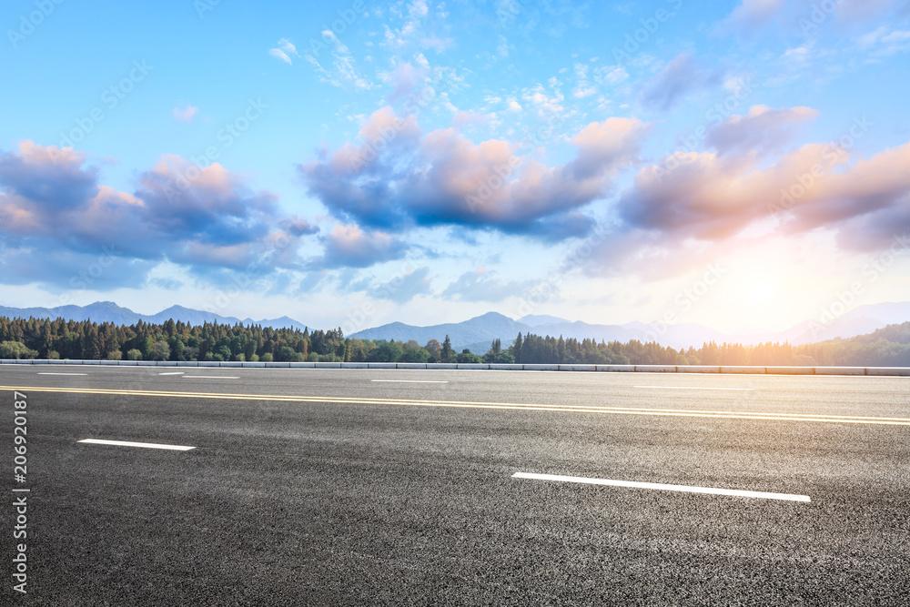 Fototapeta Asphalt road and hills with sky clouds landscape at sunset