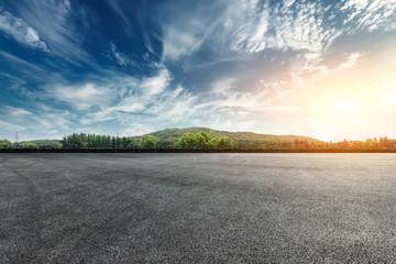 Asphalt square road and hills with sky clouds landscape at sunset