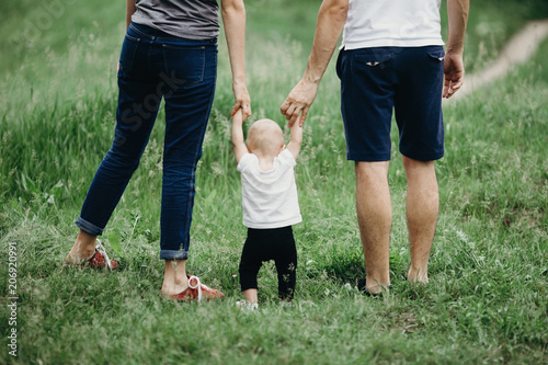Obraz Happy family walking in the park. Mom, dad and daughter walk outdoors, parents holding the baby girl's hands. Childhood, parenthood, family bonds, marriage concept - fototapety do salonu
