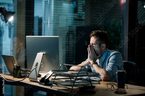 obraz PCV Man covering mouth while yawning at table in dark office having overtime.