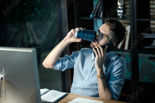 Fototapety, obrazy: Casual man filling himself with caffeine and speaking on smartphone sitting at table with computer.