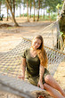 Young pretty woman wearing green dress sitting on wicker hammock with sand and palms in background. Concept of traveling to tropic islands and summer vacations in Thailand.