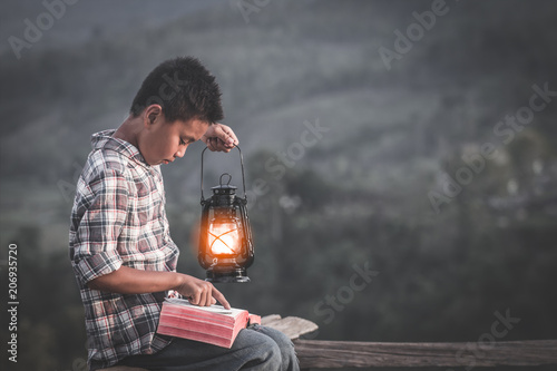 Fotografering Boy holding oil lamp and reading bible, christian concept