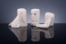 Medical Bandages With Different Size On Black Glass Table With Reflection.