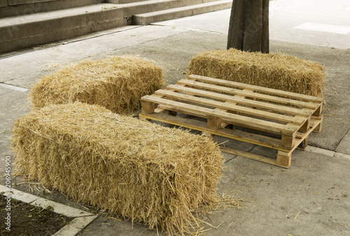 Fotografía  Mesa y asientos con elementos naturales como un palé y unas balas de paja