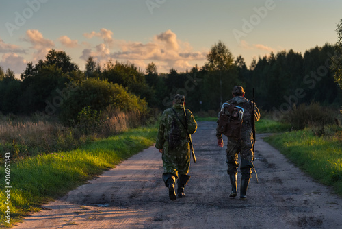 Fotografie, Obraz Two hunters go on an evening hunt
