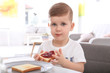 Cute little boy eating toast with sweet jam at table