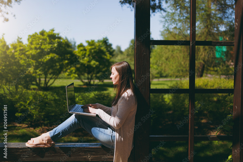 Fototapeta Young successful businesswoman in light casual clothes. Smiling Woman working on modern laptop pc computer in city park in street outdoors on spring nature. Mobile Office. Freelance business concept.