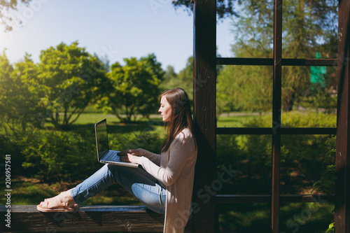 Obraz Young successful businesswoman in light casual clothes. Smiling Woman working on modern laptop pc computer in city park in street outdoors on spring nature. Mobile Office. Freelance business concept. - fototapety do salonu