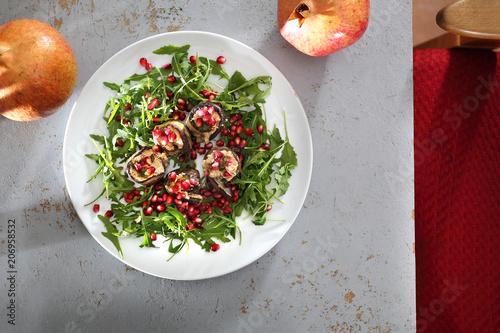 Fototapeta Sałata z grillowanym bakłażanem. Roladki z bakłażana z serem podane z owocem granatu na sałacie z rukoli. obraz