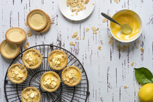 Lemon Tartlets Decorated With Toasted Almond Flakes, Unfilled Pastry Cases And A Bowl Of Lemon Butter.