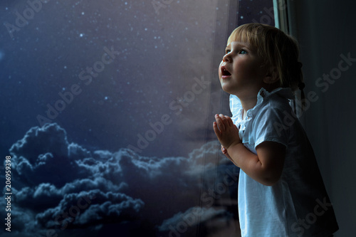 the child looks out the window into the night sky