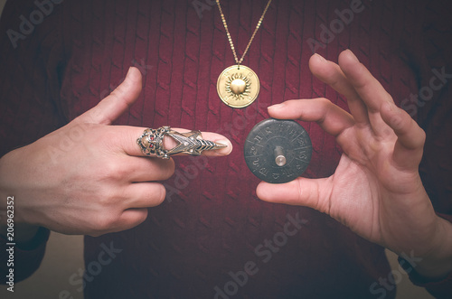 Photo Astrologer demonstrates in his hand a Zodiac talisman plate and showing on it by his index finger