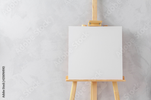 Wooden easel in the room Canvas Print