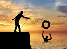 A Silhouette Of A Man Throws A Lifeline To Another Man Who Is Drowning In The Water