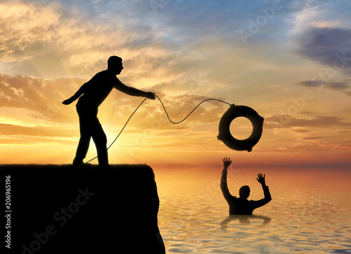 Fotografía  A silhouette of a man throws a lifeline to another man who is drowning in the wa