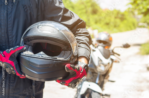 Valokuva Man in a Motorcycle with helmet and gloves is an important protective clothing f