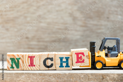 Photo Toy forklift hold letter block E in word niche on wood background