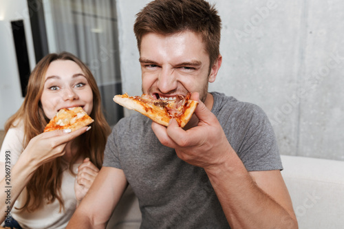 Foto op Canvas Kruidenierswinkel Close up of happy young couple eating pizza