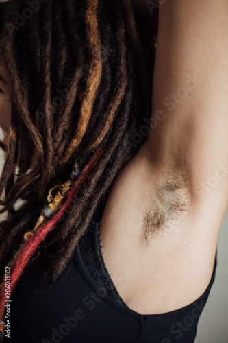 Woman with dreadlocks showing her hairy underarm