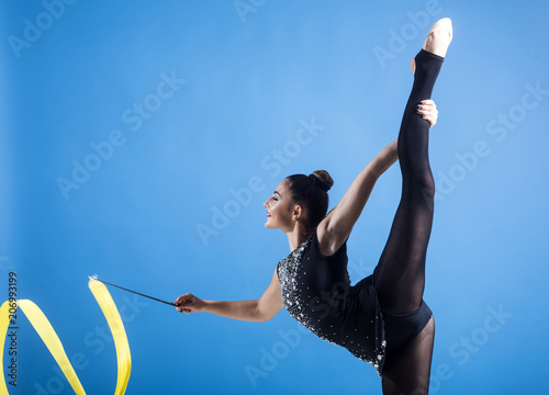 Spoed Foto op Canvas Gymnastiek Fitness and dieting of girl gymnast. Woman train acrobatics with ribbon. Workout sports activities in gym of flexible girl. Woman with ribbon for rhythmic gymnastic. Sport success and health.