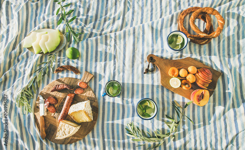 Keuken foto achterwand Picknick Flat-lay of summer picnic set with fruit, cheese, sausage, bagels and lemonade over striped blanket, top view